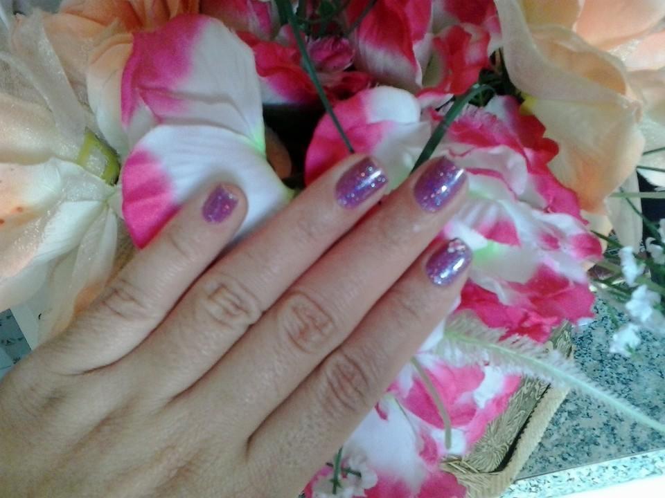 Unhas com esmaltação roxa e glitter e uma flor branca no indicador auxiliar cabeleireiro(a) designer de sobrancelhas manicure e pedicure