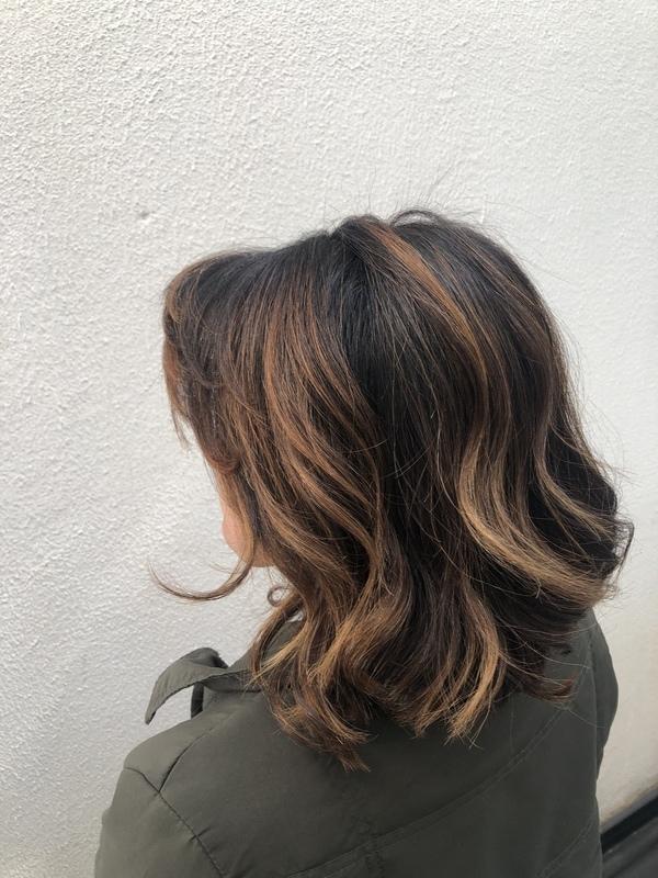 Quebra de tons escuros em cobre e corte geométrico alongado. cabelo